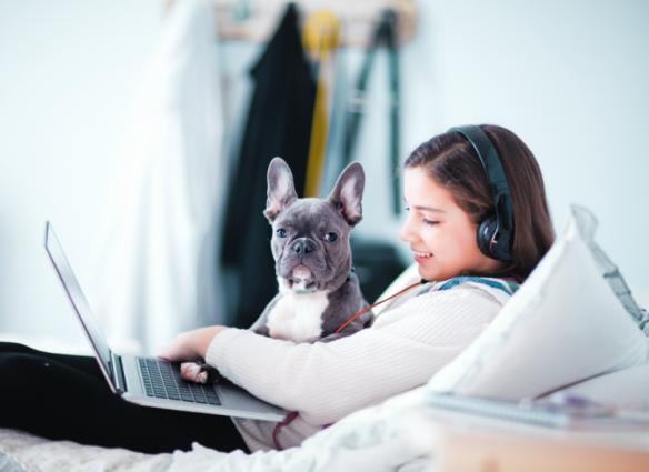 Cuarentena niña viendo computadora y audífonos con un perro